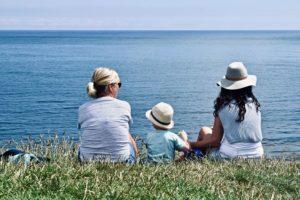 Persona mayor con familia viendo el mar